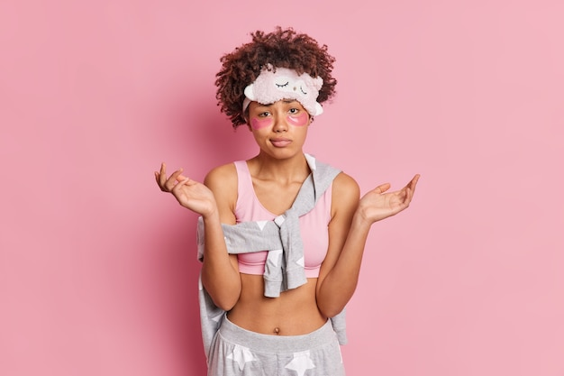 Taille-up shot van vrouw spreidt handpalmen heeft aarzelende uitdrukking past collageenvlekken toe onder de ogen om wallen te verminderen gekleed in casual pyjama geïsoleerd over roze studiomuur
