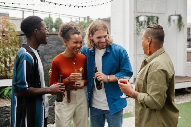 Taille-up shot van zorgeloze jonge mensen die bier drinken terwijl ze genieten van een buitenfeest met vrienden
