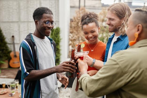 Taille-up shot van zorgeloze jonge mensen die drankjes rammelen terwijl ze genieten van een buitenfeest met vrienden