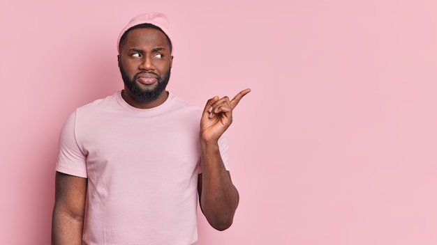 Taille-up shot van zwarte bebaarde afro-amerikaanse man geeft aan op lege ruimte iets laat zien