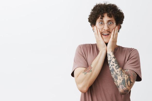 Taille-up shto van opgewonden en gelukkig geamuseerd goed uitziende jonge mannelijke hipster student in bruin t-shirt met tatoeages snor en donker krullend haar in glazen hand op gezicht houden en grijnzend van verbazing
