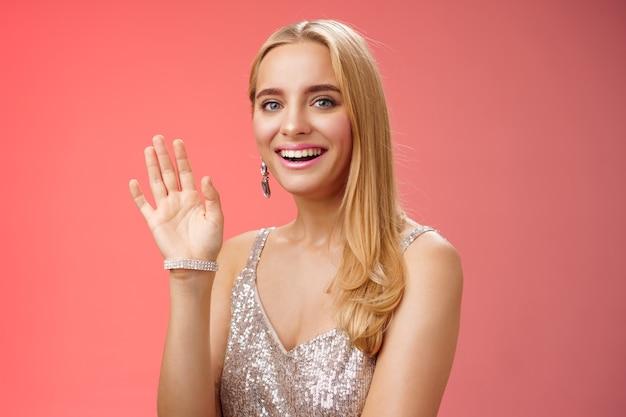 Taille-up studio-opname vriendelijke aantrekkelijke elegante tedere blonde vrouw zeg hallo zwaaiende opgeheven hand groet gastvrije vriend glimlachend opgetogen introductie van zichzelf hallo gebaar, rode achtergrond