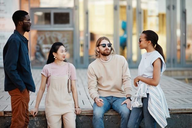 Taille-up zicht op diverse groep hedendaagse jonge mensen die buiten aan het chatten zijn in stedelijke stadsomgeving