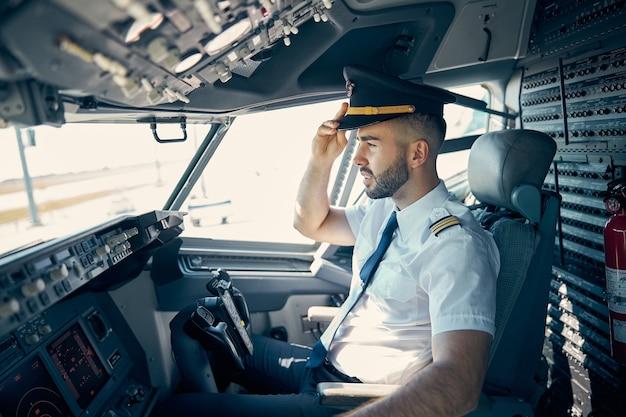 Taille-up zijaanzicht portret van zelfverzekerde mannelijke piloot in pet die naar beneden kijkt vanuit de cockpit