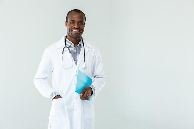Taille van glimlachende beroepsbeoefenaar die een casusrapport vasthoudt terwijl hij een patiënt verwelkomt