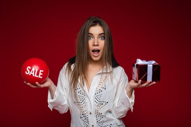 Taille van mooie dame met open ogen die rode ballon met een inscriptie verkoop en geschenkdoos houdt
