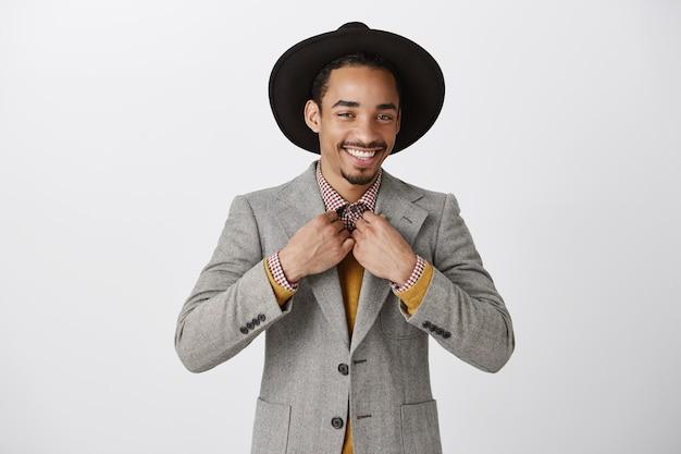 Taille van succesvolle zelfverzekerde afro-amerikaanse zakenman die brutaal kijkt, draagkostuum