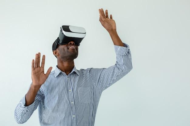 Taille van vrolijke glimlachende afro amerikaanse zakenman die vr-bril draagt terwijl hij tegen een witte muur staat