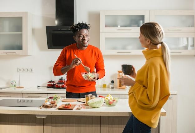Taille van vrolijke man die met een kom salade en een houten lepel terwijl zijn langharige vriendin voor hem staat met een kopje thee