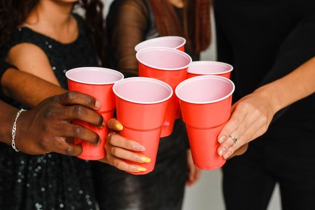 Taille van zes vrienden die plezier hebben en alcohol drinken tijdens het nieuwjaarsfeest