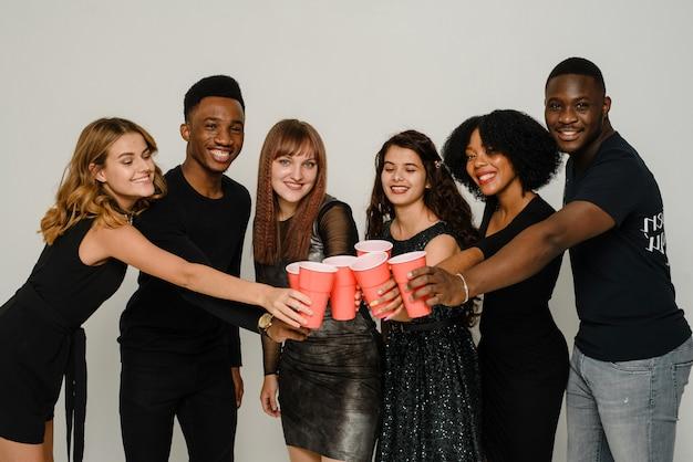 Taille van zes vrienden die plezier hebben en alcohol drinken tijdens nieuwjaarsfeest op witte achtergrond