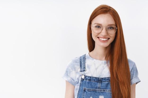 Taille zelfverzekerd knap casual roodharig meisje blauwe ogen lang rood natuurlijk kapsel, express geluk vastberaden eerste prijs ontvangen, gelukkige vrolijke stemming, staan witte muur zelfverzekerd