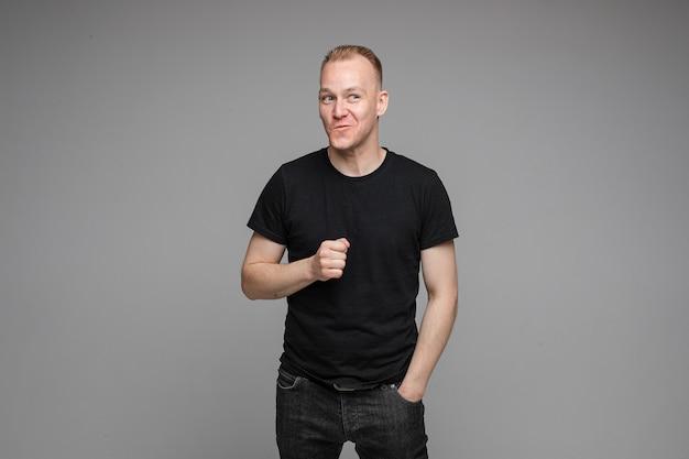 Taillefoto van een speels uitziende man in zwarte kleren die zijn vuist uitsteekt en glimlacht