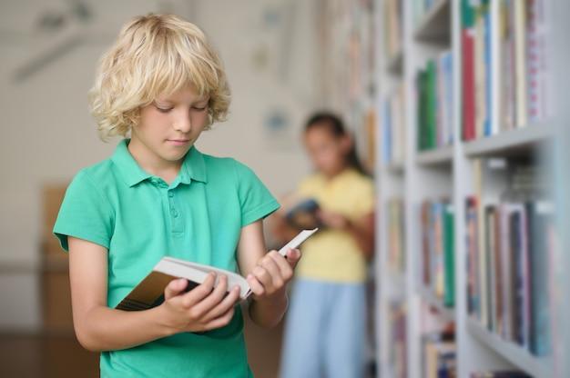 Tailleportret van een gefocuste schattige schooljongen met golvend blond haar die door een boek bladert in de bibliotheek