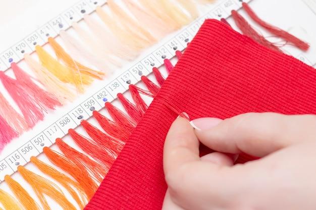 Tailor selecteert de kleur van de draad in de catalogus voor de rode stof. atelierwinkel van stoffen en accessoires.