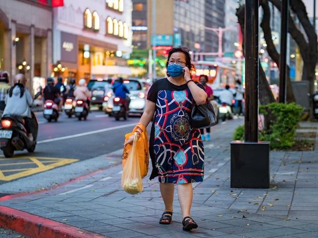 Taipei, taiwan - 14 mei: passagiers met een chirurgisch masker op 14 mei 2021 in taipei, taiwan. er zijn 160.686.749 bevestigde gevallen van covid-19, waaronder 3.335.948 doden in de wereld. Premium Foto