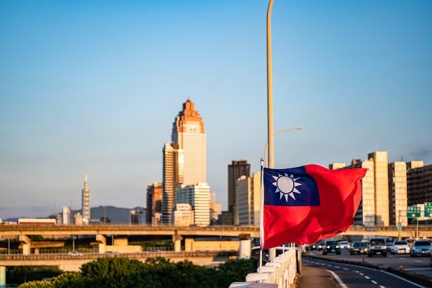 Taipei, taiwan - 4 okt 2020: de vlag van taiwan wappert in de wind. luchtpanorama over het centrum van taipei met taipei 101 skyscraper, hoofdstad van taiwan