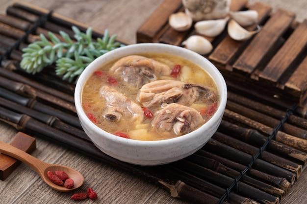 Taiwanees eten - eigengemaakte heerlijke knoflookkippensoep in een kom op donkere houten lijstachtergrond.