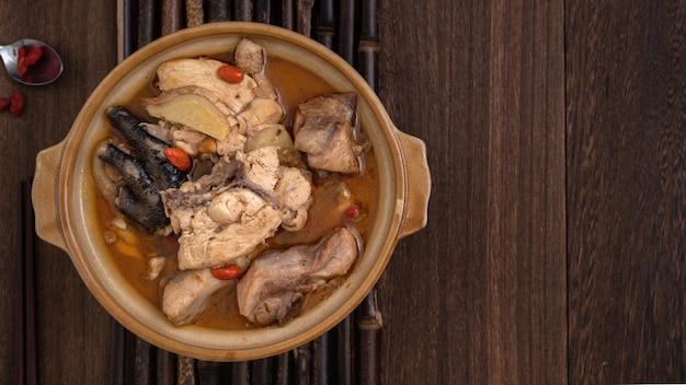 Taiwanees eten - eigengemaakte heerlijke sesamolie kippensoep in een kom op donkere houten tafel achtergrond.