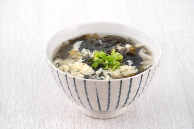 Taiwanees eten - zelfgemaakte heerlijke zeewier ei drop soep in een kom op een dienblad over lichte houten tafel achtergrond.
