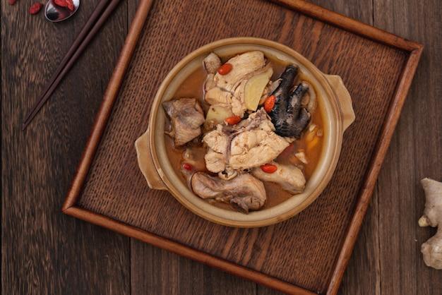 Taiwanese zelfgemaakte heerlijke sesamolie kippensoep eten in een kom op donkere houten tafel