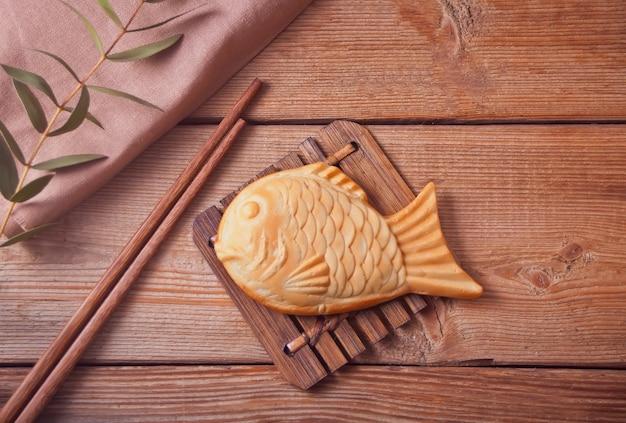 Taiyaki japanse straatvoedsel vis-vormige zoete vullende wafel op houten lijst