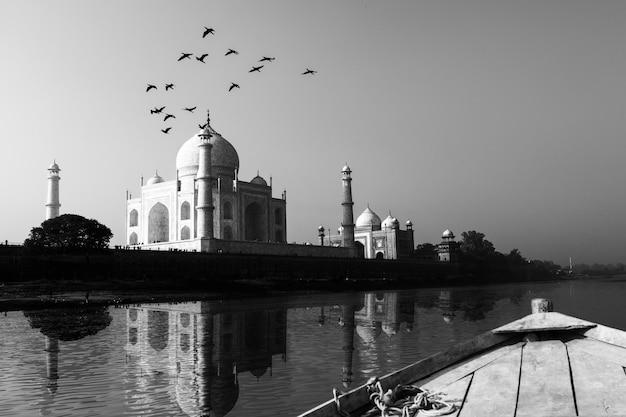 Taj mahal weerspiegeld in yamuna river-mening van houten boot in zwart-wit.