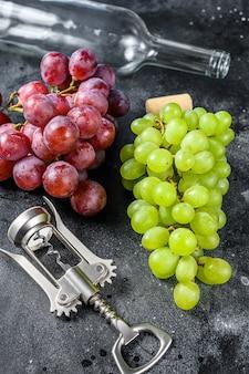 Tak van groene en rode druiven een lege fles een kurketrekker en een kurk