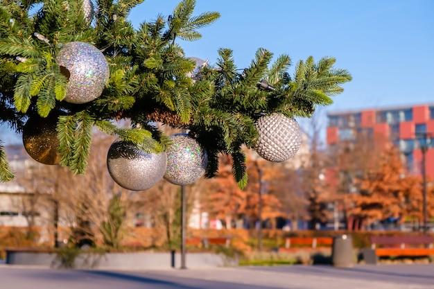 Tak van kunstmatige kerstboom met witte kerstballen op lege stadsstraat buiten op zonnige zomerdag. geen sneeuw, geen mensen.