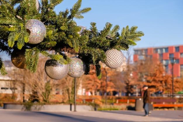 Tak van kunstmatige kerstboom met witte kerstballen op straat buitenshuis