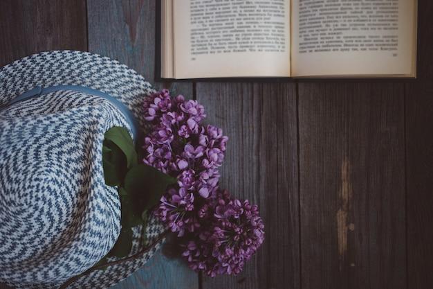 Tak van lila, de hoed en het boek op een houten achtergrond