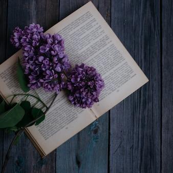 Tak van lila, op het geopende boek op een houten tafel
