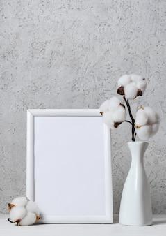 Tak van pluizige katoenen bloemen in witte vaas en wit houten frame met leeg vel papier op houten oppervlak over lichte muur. interieur bloemen compositie.