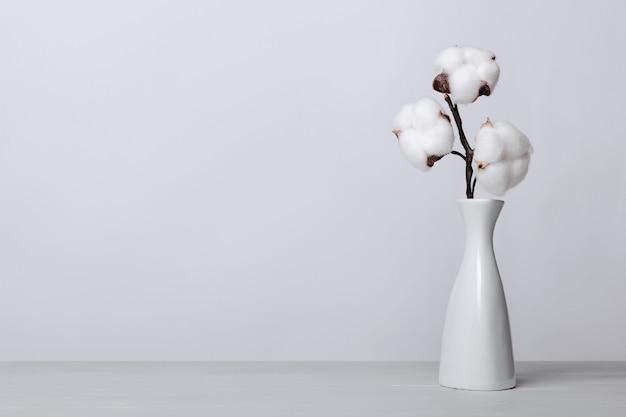 Tak van pluizige katoenen bloemen in witte vaas op licht houten oppervlak tegen een grijze achtergrond. interieur bloemen compositie.