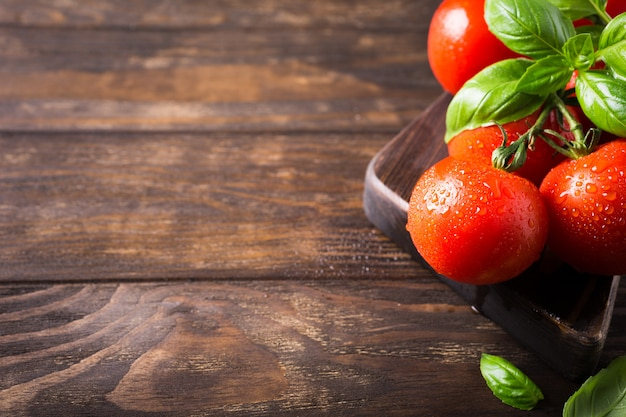 Tak van rijpe natuurlijke tomaten en basilicumbladeren