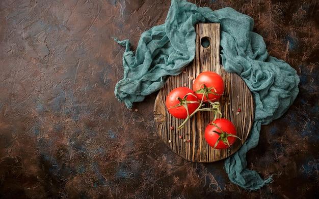 Tak van verse rijpe tomaten op snijplank. bovenaanzicht