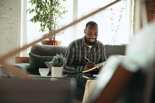 Takenlijst controleren. man, freelancer tijdens het werk in het kantoor aan huis tijdens quarantaine. jonge mannelijke zakenman die thuis blijft, zelf geïsoleerd. gadgets gebruiken. werken op afstand, preventie van verspreiding van coronavirus.
