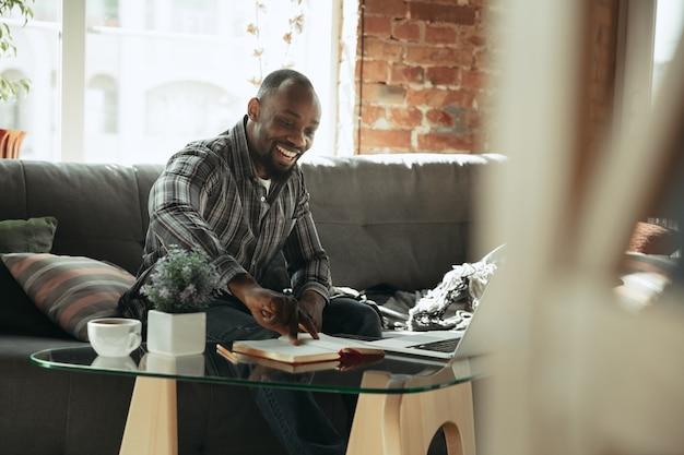 Takenlijst controleren man freelancer tijdens het werk in thuiskantoor tijdens quarantaine