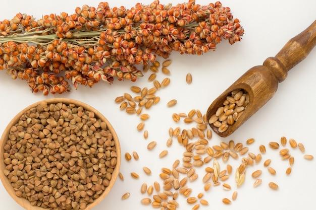 Takje sorghum, tarwe in een houten lepel boekweit in een houten kist. bely achtergrond. bovenaanzicht