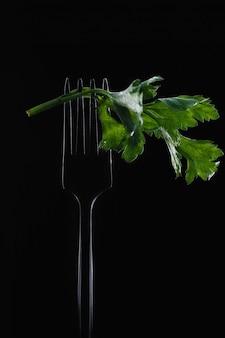 Takje verse groene peterselie op een vork op een zwarte achtergrond