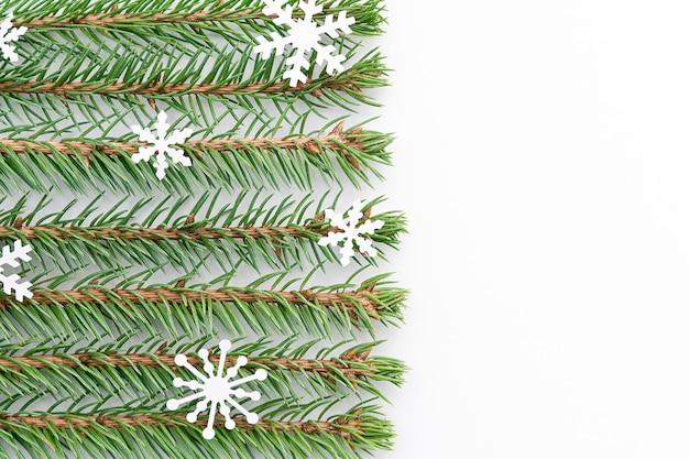 Takjes blauwe spar met sneeuwvlokken zijn horizontaal gerangschikt in even rijen op een witte achtergrond.