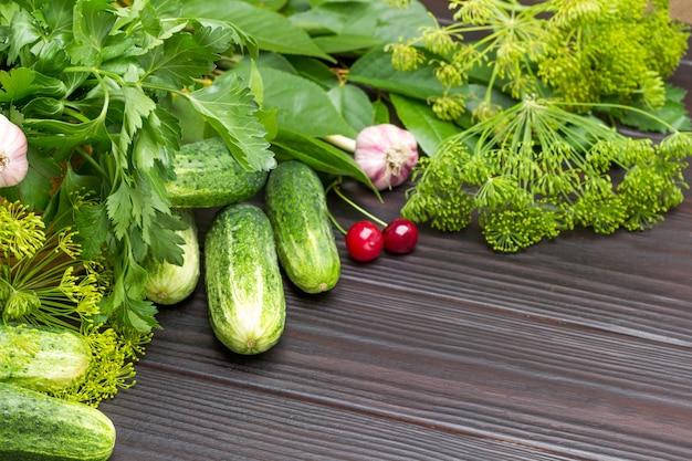Takjes dille en peterselie, ñ komkommer, knoflook en kersenbessen. ruimte kopiëren. houten achtergrond. bovenaanzicht.