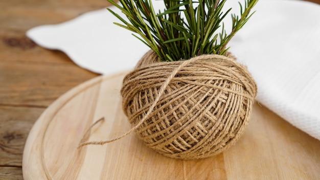 Takjes rozemarijn en strengen jute touw op een houten plank om te snijden. rustieke stijl. kruid