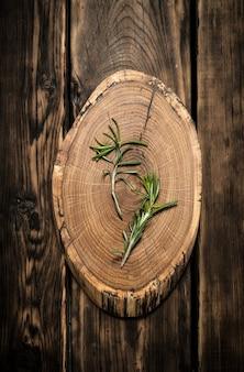 Takjes rozemarijn op een houten stam. op houten achtergrond.
