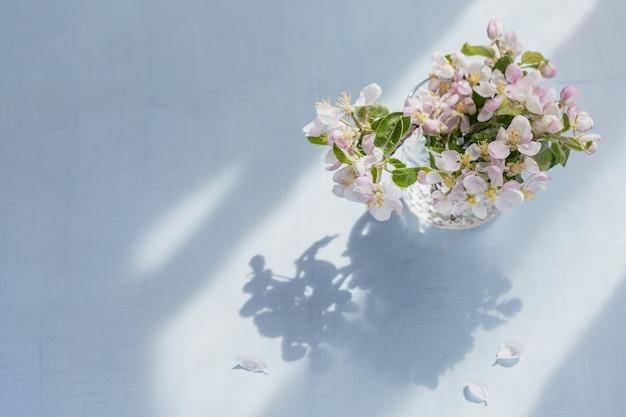 Takken met witte appelbloemen in een transparant glas op een lichtblauwe ondergrond