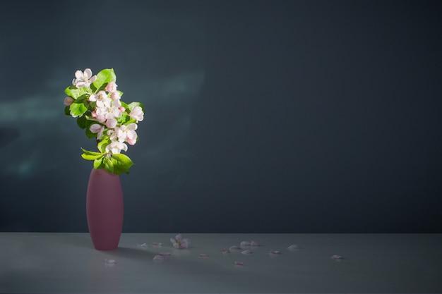 Takken van appelboom met bloemen in roze vaas op oppervlakte blauwe muur