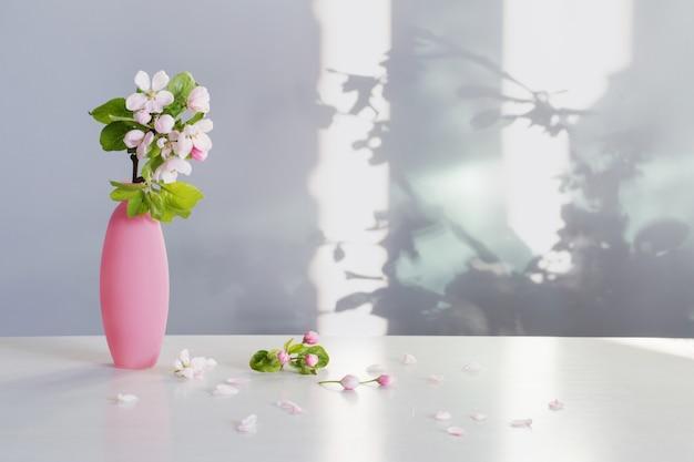 Takken van appelboom met bloemen in roze vaas op witte tafel