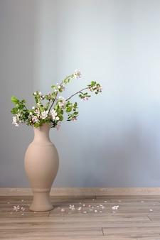 Takken van appelboom met bloemen in vloervaas tegen grijze muur