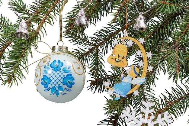 Takken van dennenboom met speelbal, bel en andere kerstversiering op een witte geïsoleerde achtergrond.