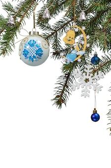 Takken van dennenboom met speelgoed bal, klokken en andere kerstversiering op witte geïsoleerde achtergrond.